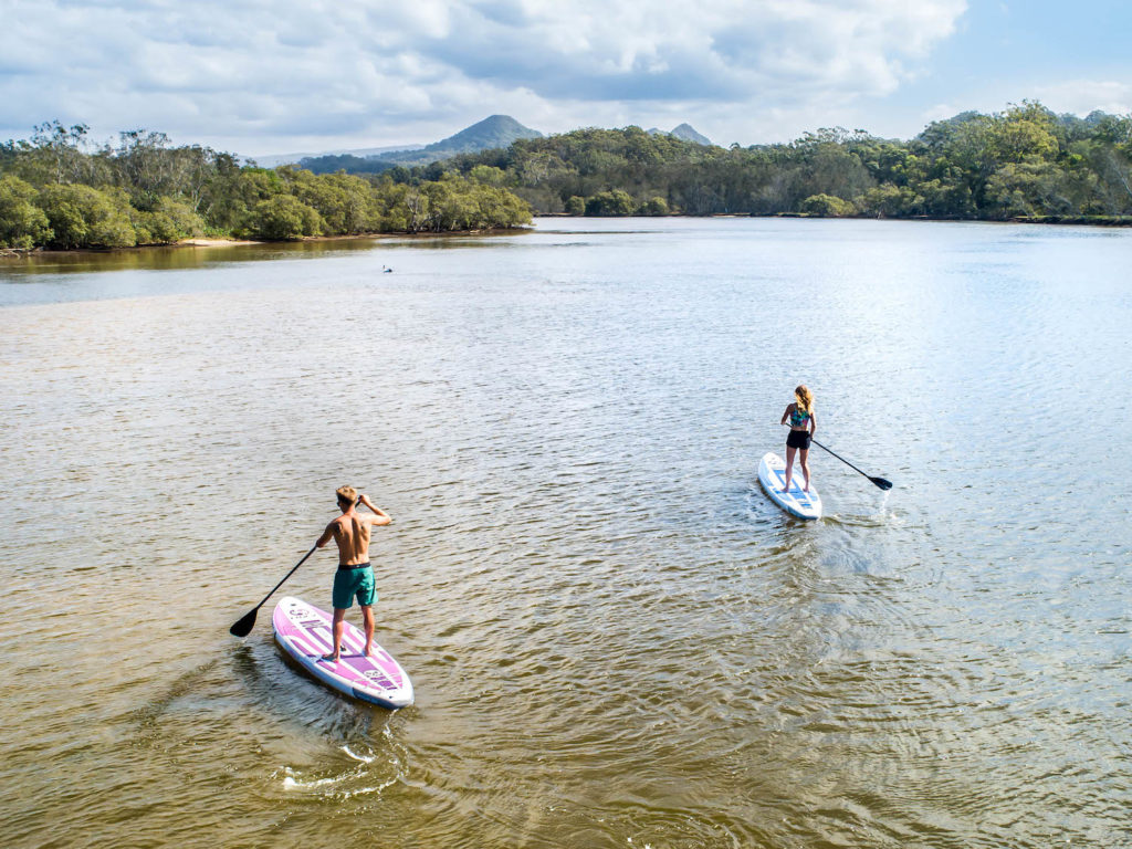 Two Nixy SUPs paddle in river